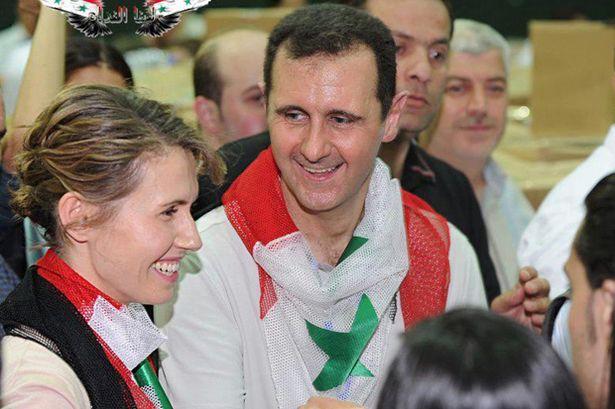 President Bashar al-Assad and his wife Asma, with the national flag around their necks